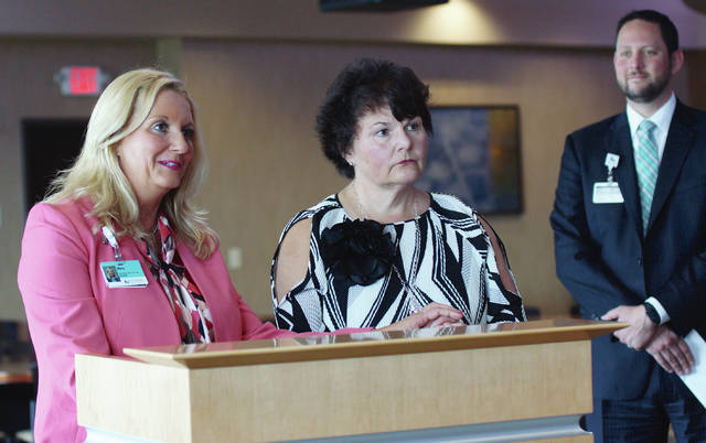 Mary Cockerham addresses the crowd at Soin Medical Center, while Dr. Sheila Manion and President Rick Dodds look on.