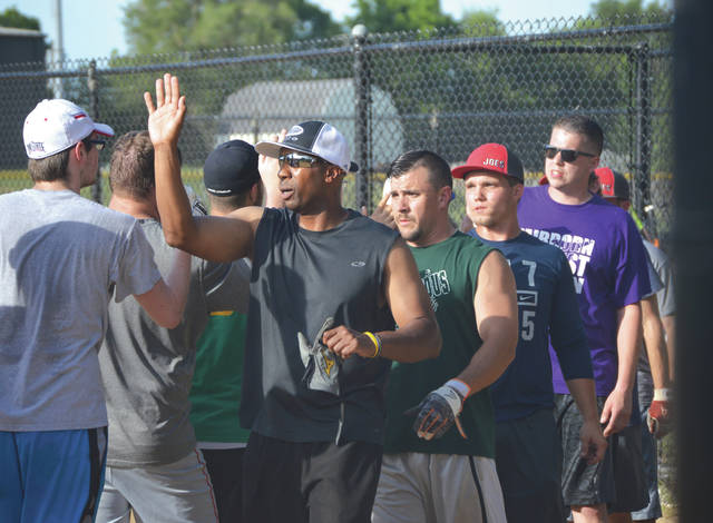Members of the Anonymous Joe's and Absher Automotive Men's D League softball teams offer each other congratulations after Friday's 6 p.m. game at Beavercreek's Rotary Park.