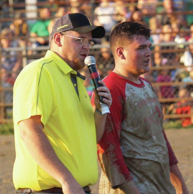 Event announcer and auctioneer Doug Middleton of Mike's Auction Service talks with a muddied Brad Eakle of Jamestown after Sunday's July 30 Calf Scramble at the Greene County Fair in Xenia. Eakle grabbed one of the three calves that were literally up for grabs.