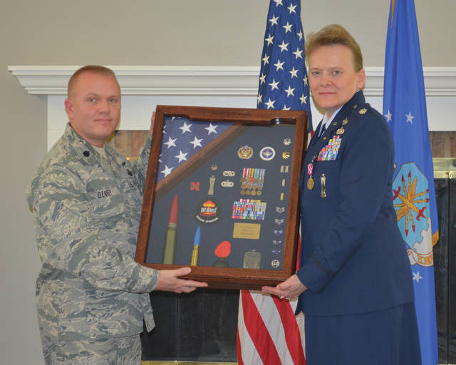 Submitted photo Lt. Col. Gary Denney, Air Force Reserve Officer Training Corps Detachment 643 commander, presents Lt. Col. Kathy Goforth a shadow box containing numerous mementos from her career. The American flag was flown over the U.S. Capital and the University of Nebraska Memorial Stadium in honor of Goforth's 33 years of service.