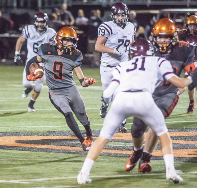 Beavercreek's Drew Nanda (9) follows the block of Beavers center Robby Holstein (70), during the first half of Thursday night's Sept. 14 game at Beavercreek High School's Frank Zink Field. In the second overtime, Nanda scored the winning touchdown to earn the Beavers a 41-35 win.