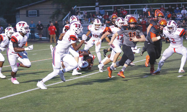 Beavercreek quarterback Cody Hocker (11) runs away from a swarm of Huber Heights Wayne tacklers, during Friday's Oct. 6 Greater Western Ohio Conference, National East matchup at Frank Zink Field. Wayne won the contest, 42-14.