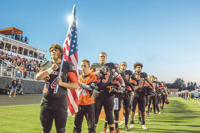 "Beavercreek senior Christopher Moore (64) holds the American flag during the playing of ""The Star-Spangled Banner,"" prior to the start of their Oct. 20 home game with Miamisburg."