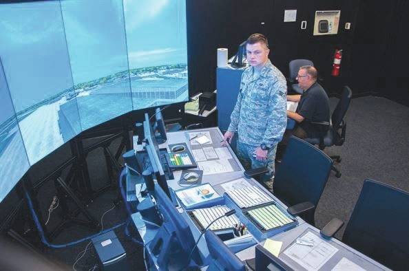 Submitted photo Senior Airman Zachary Cinnamon, 88th Operations Support Squadron air traffic controller, runs through an air traffic control scenario on Wright-Patterson's simulator as Jack Wilson, Air Traffic Control Tower Simulator administrator, operates the simulator behind him.