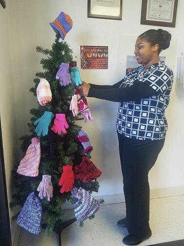 Greene County Public Health front desk staff member Michele Anderson puts hats, gloves, and scarves on the Mitten Tree.