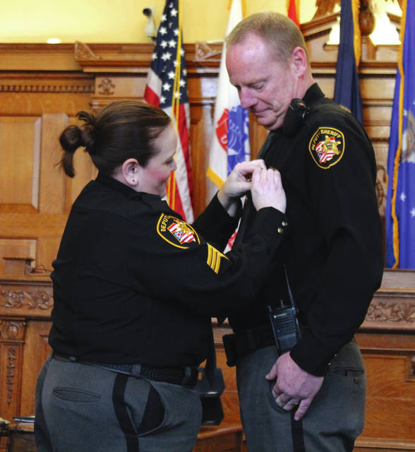 Following tradition, Sgt. Beth Prall pins a badge on her husband, Capt. Shawn Prall, during the swearing-in ceremony.