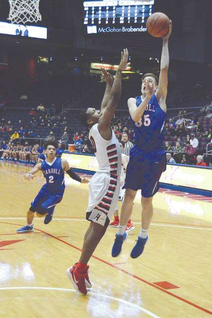 Sophomore Jaden Dahm puts up a hook shot over Shawn Hawkins (0) of Hughes, Thursday March 8 at UD Arena in Dayton.