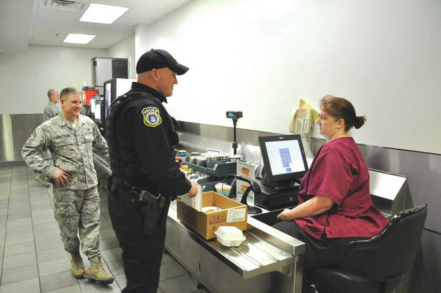 "Submitted photo Nancy Williams, Pitsenbarger Dining Facility cashier, rings up Officer Ryan Gray's main entrée ""to go"" while Chief Master Sgt. Thomas Christopher looks on at the Pitsenbarger Dining Facility located in Building 1214, Area A, Kittyhawk."