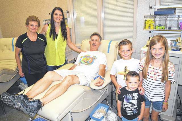 Submitted Photo McBride donates blood for the 100th time with family support.