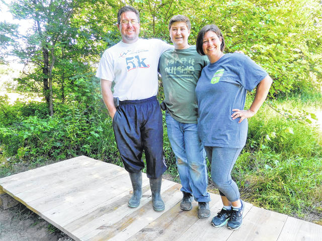 Submitted photos Mason Blount, center, stands with his parents on the completed low walk bridge. Blount is the first person in their family to achieve Eagle Scout status.
