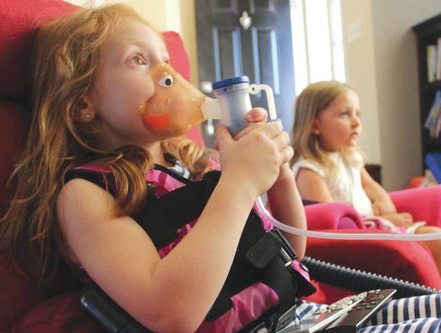 Submitted photo Five-year old Aubrey Inman watches television during a treatment for cystic fibrosis while her sister, three-year old Adalyn, keeps her company. At least twice a day, Aubrey is required to take several medications, use a nebulizer and wear a vest that that fills with air and pulses around the body to shake up the lungs to help break up the mucus.
