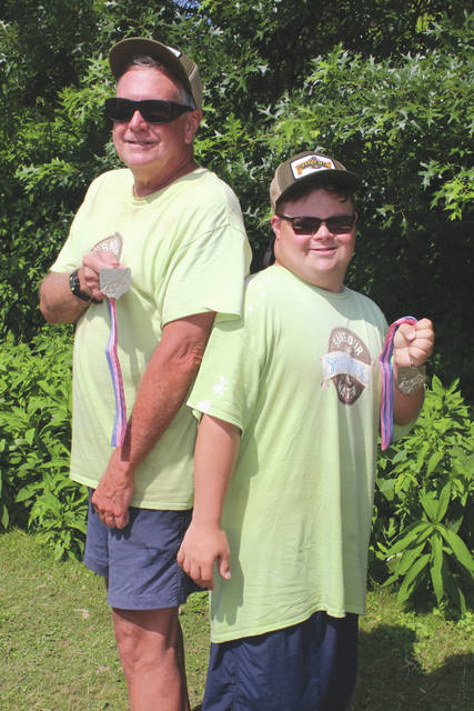 Mike Chard (left) and his son Dylan pose back-to-back with their medals in recognition of winning a state paddling title two years in a row, July 28 at the U.S. Canoe Association Ohio Championships, in Fairport Harbor.