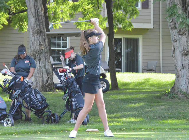 While teammates Megan Diltz and Zoe Romaker grab their clubs for their tee shots, Beavercreek's Ally Barnett hits a drive off a Par-3 hole Wednesday Aug. 29 during a Greater Western Ohio Conference girls high school match with Vandalia Butler at Beavercreek Golf Club.